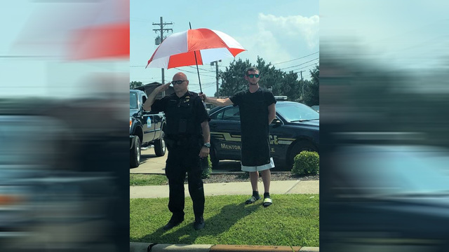 Photo of man holding umbrella over Ohio officer during funeral procession goes viral